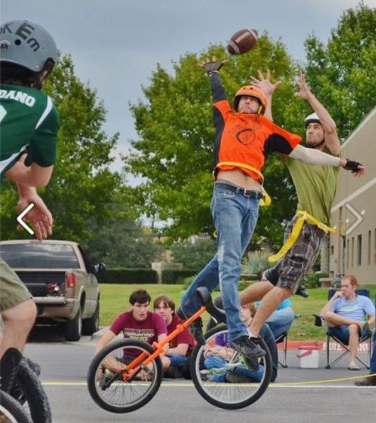 Two unicycle footballers scramble for the ball